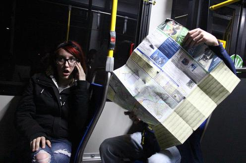Woman talks on phone while man looks at map