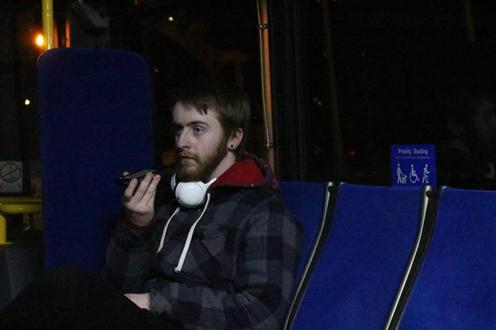 Man sits on bus, talking into a walkie-talkie