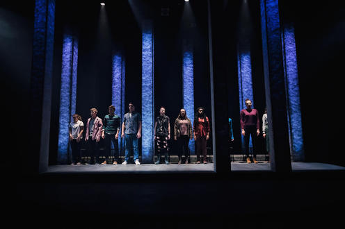 Full cast in a line onstage