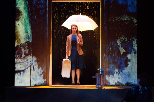 Eurydice standing in an elevator with an Umbrella