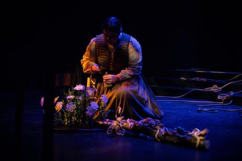 An actors is knelling before some flowers