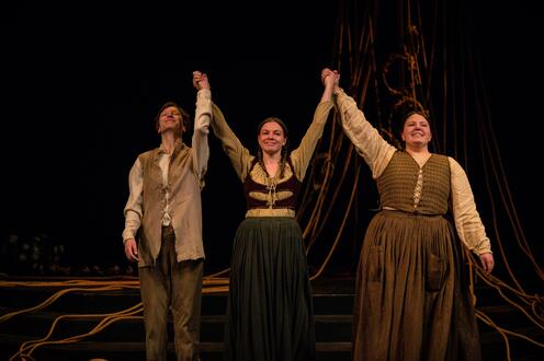 Three actors are one stage holding hands. Their arms are raised. They are about to bow
