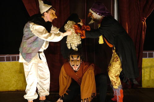 Actors in a group wearing masks on stage