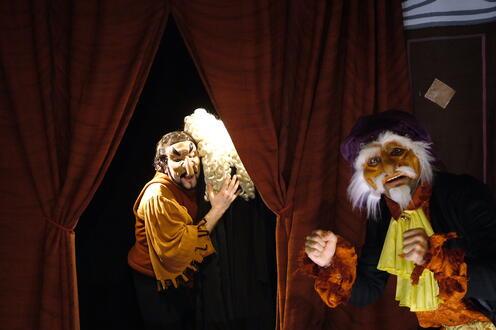 Actors in masks looking forward