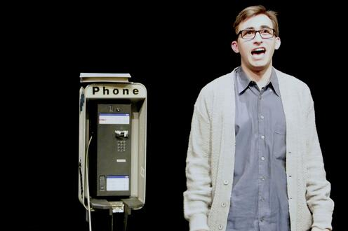Simon stands on stage beside a pay phone