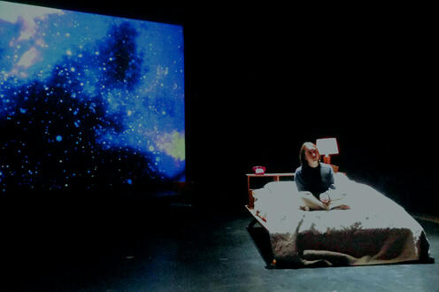 A bed is on stage and stars are projected behind