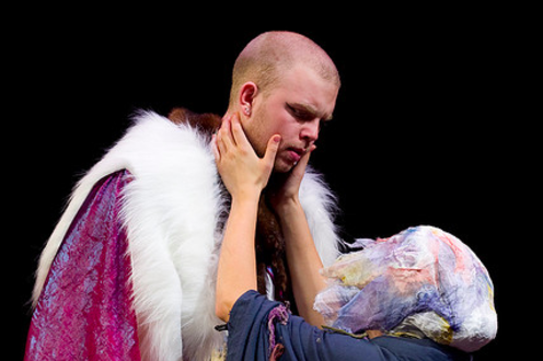 Person kneeling and embracing another person in the play 'Julius Caesar'