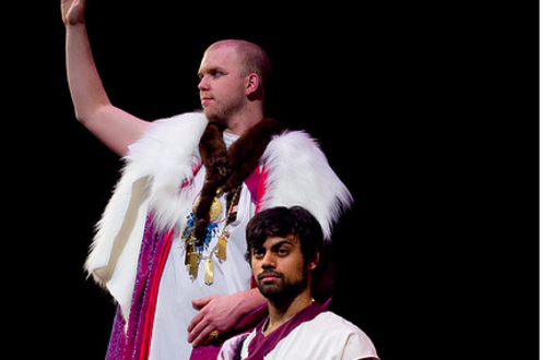 A scene from the play 'Julius Cesar' in which two men are dressed in roman robes with one on his knees