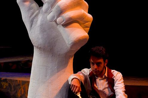 Man sitting holding knife in the play 'Julius Caesar'