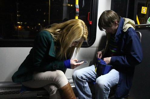 Man and woman text on bus