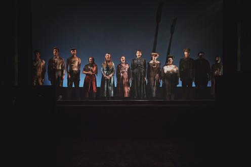 The full cast is standing on stage