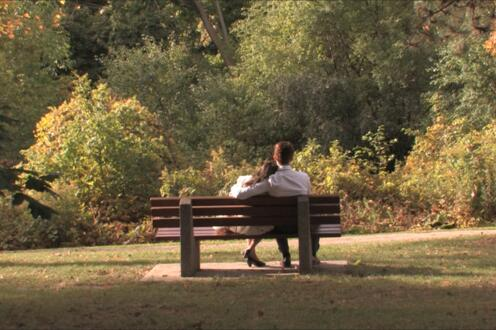 Eurydice and Orpheus sitting on a bench outside
