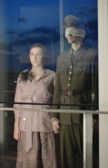 Woman and soldier looking through a window with clouds reflected