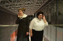 Two women in turn of the century dress listening to ear phones