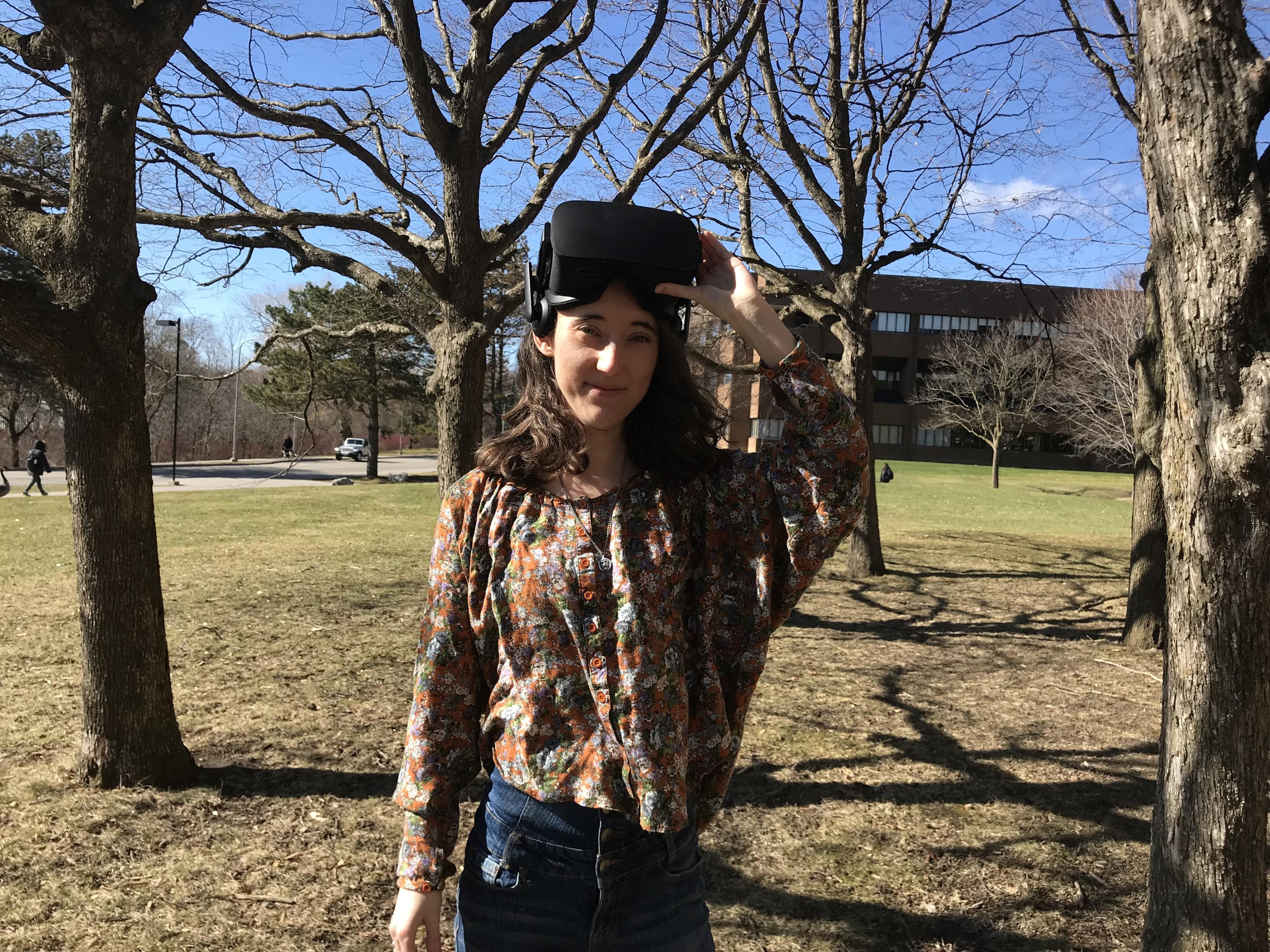Jessica Bertrand outside in a stand of trees with VR goggles