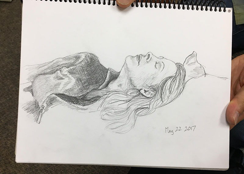 Pencil portrait of a woman lying on a bed