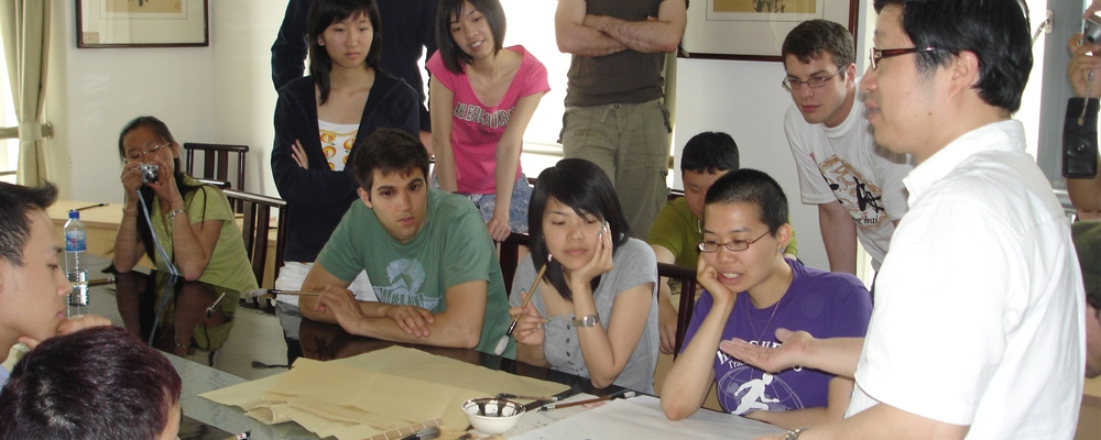 students listening to a teacher while looking at a poster of chinese calligraphy characters