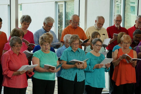 a choir group standing and singing