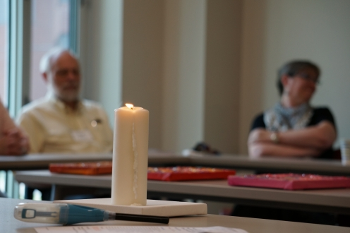 a group of people in a classroom talking with a candle in the foreground