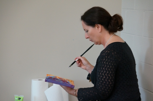 a woman holding a canvas and paintbrush
