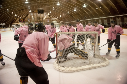 Warriors in pink shirts playing hockey