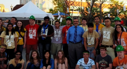 President Feridun with students in front of art project trees