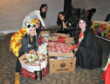 Students in costumes with canned food