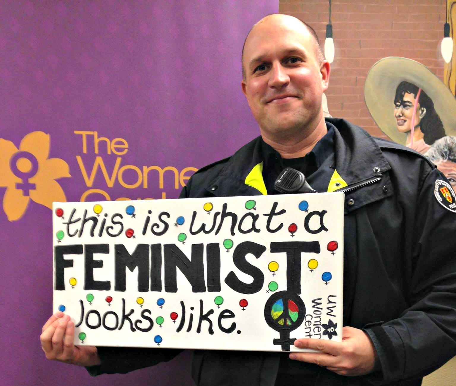 "Man holding up sign that reads: ""this is what a feminist looks like"""