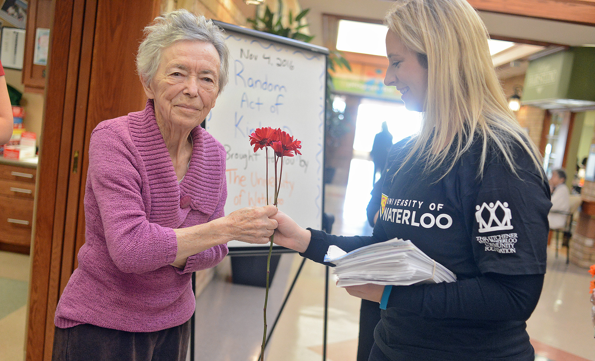 Students sharing flowers with elderly