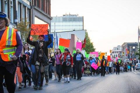 Individuals marching in front of Kitchener City Hall for Take Back the Night