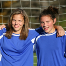 two girls on a soccer pitch in uniform.