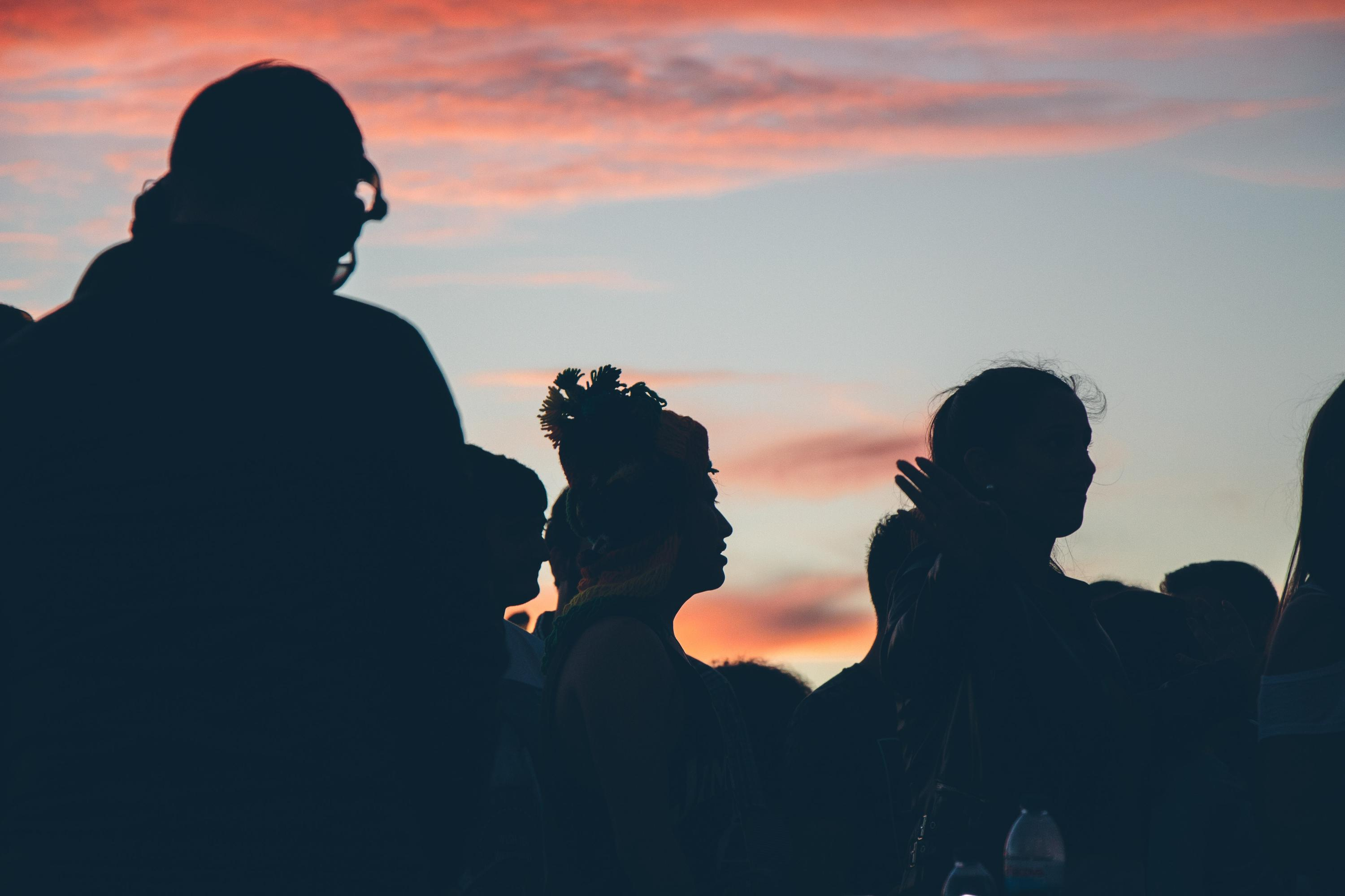 silhouettes of a crowd of people at sunset