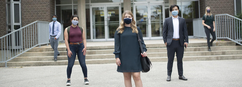 People-standing-outside-building-wearing-masks