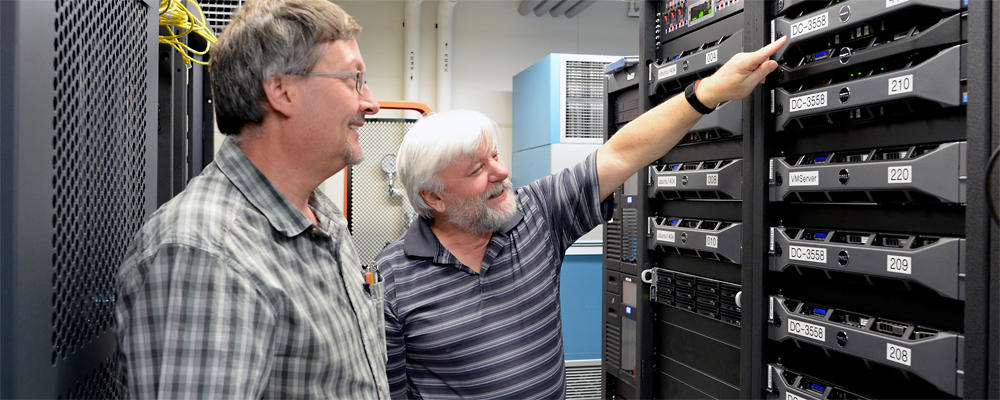Two staff members (Dan and Dave) are looking at a server rack.