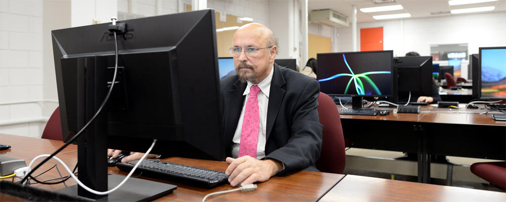 Staff member (Ed) looks at a computer display in a lab.