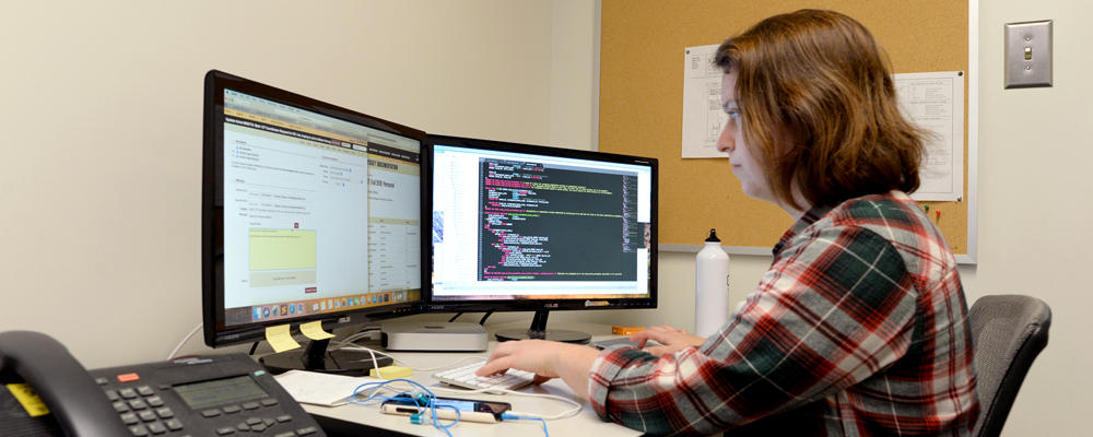 A co-op student (Jamie) works on some code at a mac workstation.