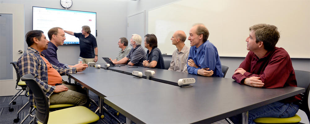 9 staff members sit around a meeting table, looking at a large display.