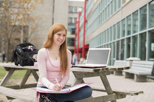 female student studying outside on a park bench