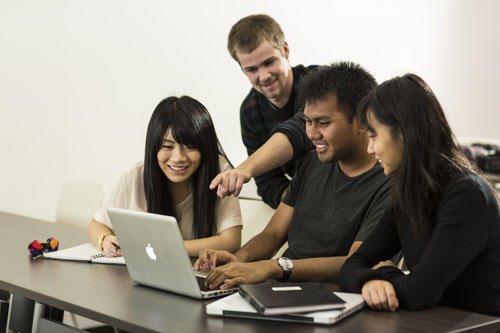four students working from a lap top