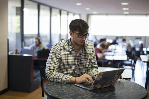 Graduate student working off laptop in lounge area