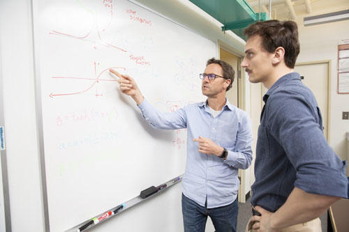 Professor and student solving a problem on a white board