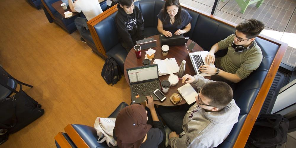 Birds eye view of five students studying at a round table