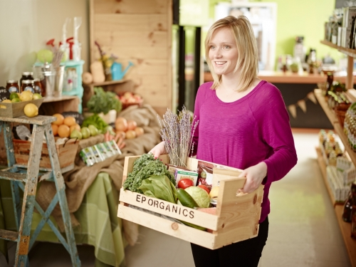 Emily Peat holding a crate of fresh vegetables labeled EP Organics, in the Eat Green Organics store