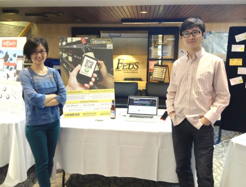 Rachel Huang and Peter Chen with a table, poster and laptop