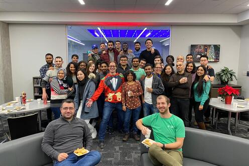 Group picture of full-time MBETs in the Conrad Hub for the winter holidays.