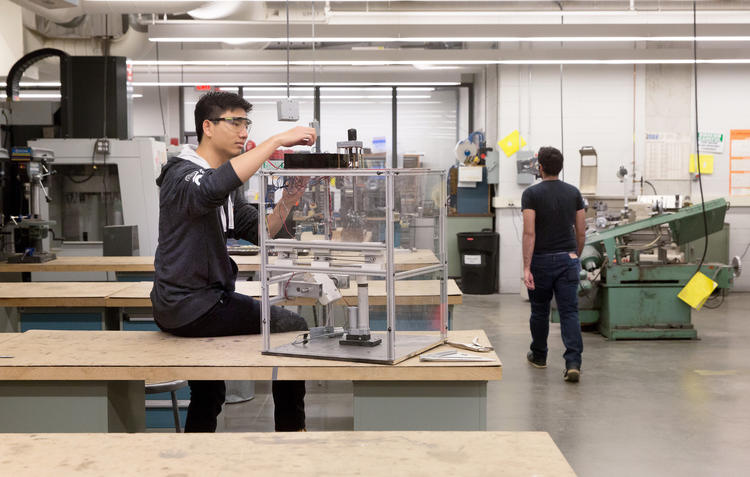 Richard Yim working on a robot in engineering