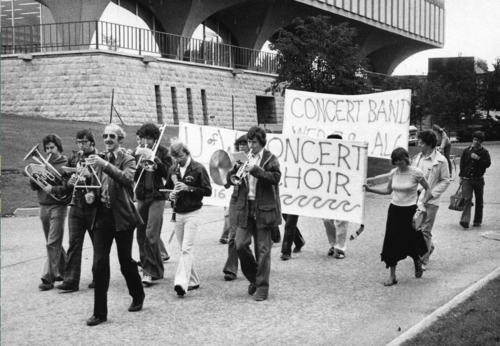 Proudly playing a triangle, Alfred Kunz leads a parade of musicians around campus in 1977.