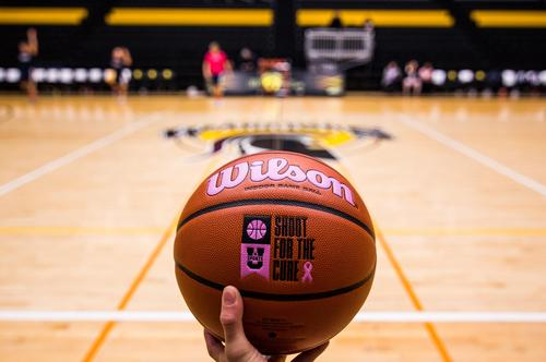 "A basketball emblazoned with a ""shoot for the cure"" logo is held up in front of the Warriors basketball court."