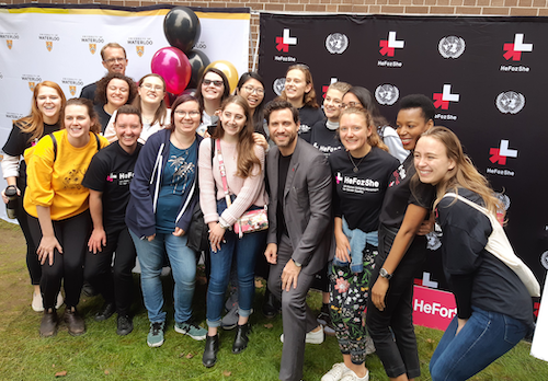 Students and staff pose for a group photo in front of a HeForShe banner.