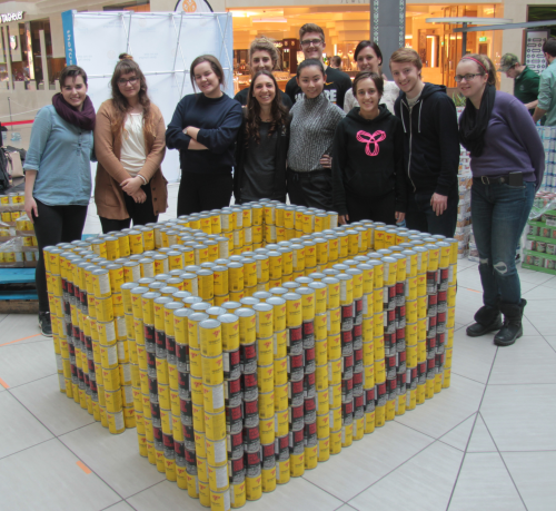 "Student volunteers and their can sculpture that spells ""UW 60"" and is formed in the shape of the number 60."